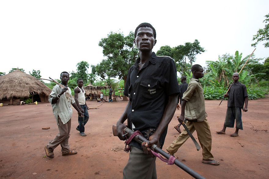 10 May 2010 - Yambio, Western equatoria State, South Sudan - Arrow Boy patrolling with home made gun. Western Equatoria State has suffered years of attacks by the Lord's Resistance Army. Thousands of civilians have been displaced and hundreds killed or abducted in the border area between Southern sudan, DRC and the Central African Republic. In the absence of an effective response by the Sudanese government to the Lord's Resistance Army, many local men and boys have organized self-defense forces known as the Arrow Boys who battle the relatively well-armed LRA with traditional weapons such as bows, arrows, spears and clubs, treated with poisonous. Initially the self defense force was at a small scale, and it grew up in September 2009 when backlash attacks started to kill, loot, burn houses and rape the villagers. Today, the Arrow boys played a brave and crucial role by taking in charge the protection of their villages. Photo credit: Benedicte Desrus