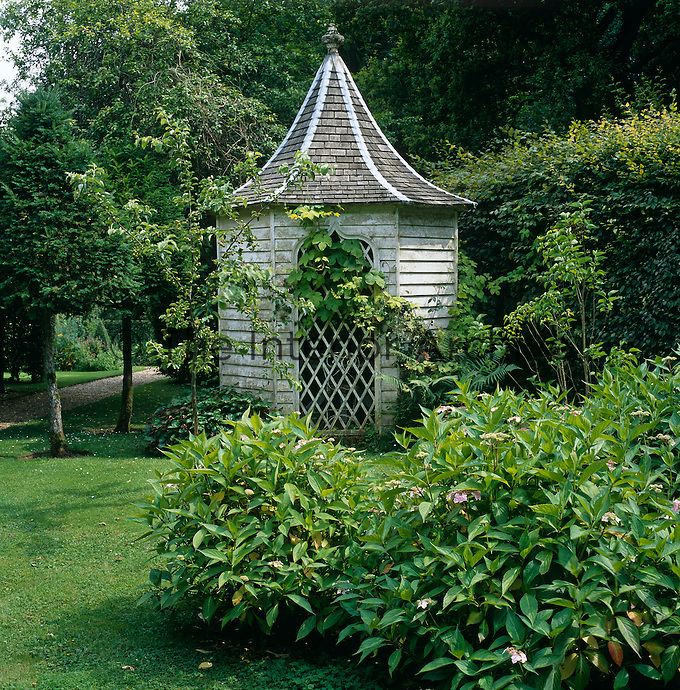 Side view of the wooden gazebo with a pepper-pot roof and gothic window concealed amidst the foliage of the garden