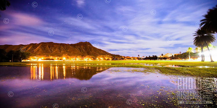 A reflection of Diamond Head in a flooded Kapi'olani Park at night; moonlit clouds and stars are visible in this 30-second exposure.