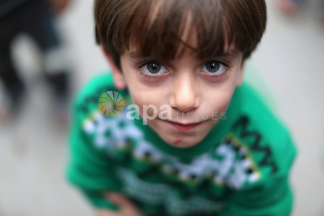 A Palestinian boy poses for a photograph at the market in Shati refugee camp in Gaza city on Jan. 07, 2016. Photo by Ezz al-Zanoun
