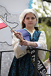 Greek Parade in New York City. A girl in a costume, on a float, waves flags in the Greek Parade in New York City.