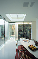 The kitchen/dining area is flooded with light from a central skylight and the floor to ceiling glass walls