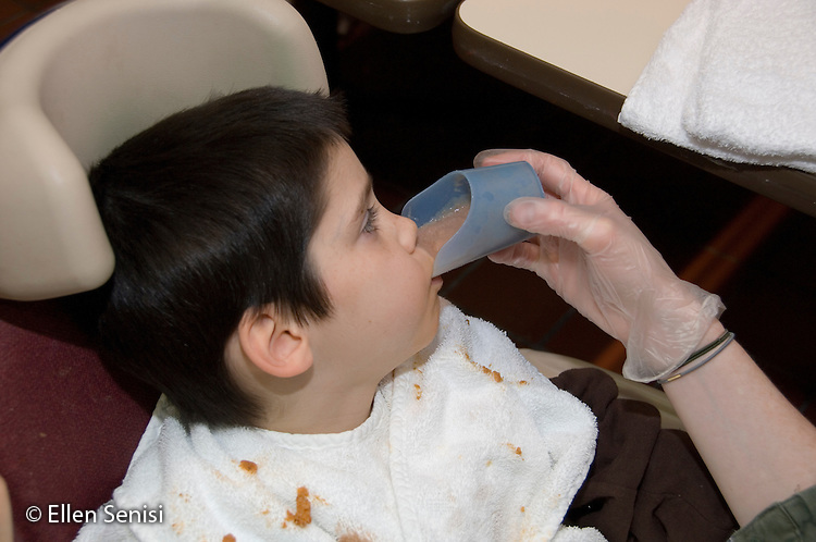 MR / Albany, NY.Langan School at Center for Disability Services .Ungraded private school which serves individuals with multiple disabilities.Child is given chocolate milk to drink in a cut-out nose cup. Childs liquids are thickened to make them easier to drink. Student wears clothing protector to help stay clean while dining. Boy: 8, cerebral palsy, spastic quadriplegic, nonverbal with expressive and receptive language delays.MR: Hac2.© Ellen B. Senisi