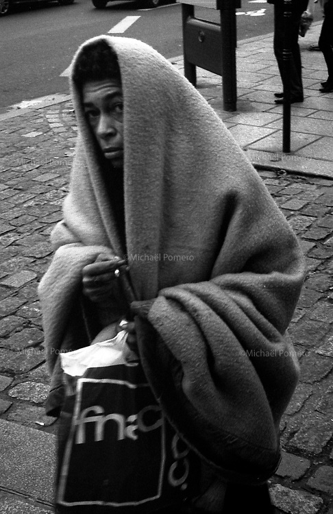 Paris (île de france)<br /> <br /> Femme sans abris marchant avec une couverture sur elle.<br /> <br /> Homeless woman walking with a blanket over her.