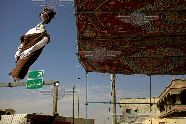 An effigy of Col. Muammar el-Qaddafi (Gaddafi) swings from a  rebel checkpoint in Misurata.