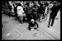 An elderly Hong Kong Chinese beggar pleads for money in front of a street vendor selling cheap clothing at Mongkok district, Kowloon, Hong Kong, 1983.