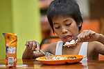 A boy enjoys a meal in Knox United Methodist Church in Manila, Philippines. The church offers food to hungry people in its neighborhood.