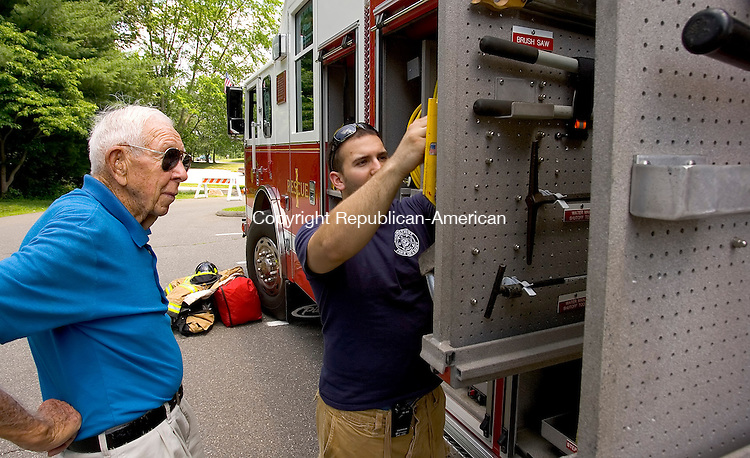 SOUTHBURY, CT --JUNE 28, 2008-062808JS04-Southbury Volunteer Firefighter Derrek Guertin, right, shows rescue apparatus to Heritage Village resident Mel Biedermann, left, during a road show open house at Heritage Village on Saturday. This is the first time the department has taken its equipment on the road for this type of showing but the idea was to aquaint the villagers with the department. <br /> Jim Shannon/Republican-American