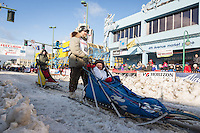 Lev Shvarts and team leave the ceremonial start line with an Iditarider at 4th Avenue and D street in downtown Anchorage, Alaska during the 2015 Iditarod race. Photo by Jim Kohl/IditarodPhotos.com