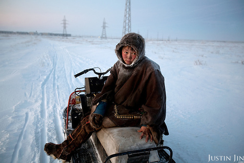 Reindeer herder Simyon travel hours by sled from his tent in the tundra to buy supplies at the village shop in Sovetsky..Construction of gas pipelines in the tundra is threatening the herders' way of life, forcing them to travel further afield in search of pastures.Vorkuta is a coal mining and former Gulag town 1,200 miles north east of Moscow, beyond the Arctic Circle, where temperatures in winter drop to -50C. .Here, whole villages are being slowly deserted and reclaimed by snow, while the financial crisis is squeezing coal mining companies that already struggle to find workers..Moscow says its Far North is a strategic region, targeting huge investment to exploit its oil and gas resources. But there is a paradox: the Far North is actually dying. Every year thousands of people from towns and cities in the Russian Arctic are fleeing south. The system of subsidies that propped up Siberia and the Arctic in the Soviet times has crumbled. Now there's no advantage to living in the Far North - salaries are no higher than in central Russia and prices for goods are higher.