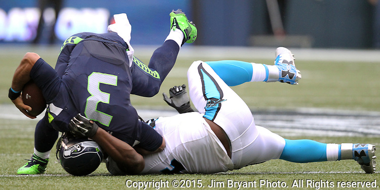 Seattle Seahawks  quarterback Russell Wilson is turned on his head by Carolina Panthers defensive end  Kony Ealy (94) at CenturyLink Field in Seattle on October 18, 2015. The Panthers came from behind with 32 seconds remaining in the 4th Quarter to beat the Seahawks 27-23.  ©2015 Jim Bryant Photography. All Rights Reserved.