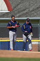 State College Spikes third baseman Ronnierd Garcia (40) smiles after being thrown out on a great defensive play as he hands his helmet and gloves to coach Roger Lafrancois (48) during a game against the Batavia Muckdogs August 23, 2015 at Dwyer Stadium in Batavia, New York.  State College defeated Batavia 8-2.  (Mike Janes/Four Seam Images)