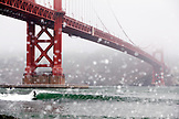 USA, California, San Francisco, a surfer catches a wave at Fort Point beneath the Golden Gate Bridge
