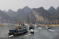 Tour boats in one of China's most famous landscapes - the dramtic karst limestone hills formed by the Li Rver in Guilin, China. Due to the sheer volume of tourists, the dozens of boats are required to travel in a single daily convoy from Guilin to Yangshou..04 Oct 2006