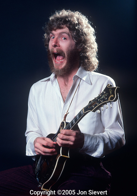 "Sam Bush, March 1982. American bluegrass mandolin player considered an originator of the Newgrass style with Newgrass Revival. He has extended the possibility of the instrument as a premier Nashville Session player. Sam did tour with Harris' band, The Nash Ramblers. Additional collaborations include recording and live performances with many virtuoso musicians and artists such as Doc Watson, Linda Ronstadt, Dolly Parton, Ann Savoy, Tony Rice, Peter Rowan, Russ Barenberg, David Grisman, Mark O Connor, Edgar Meyer, and importantly; ""Strength in Numbers"", a band consisting of Bela Fleck, Tony Rice, Mark O Connor, Edgar Meyer, Jerry Douglas, and Sam Bush."