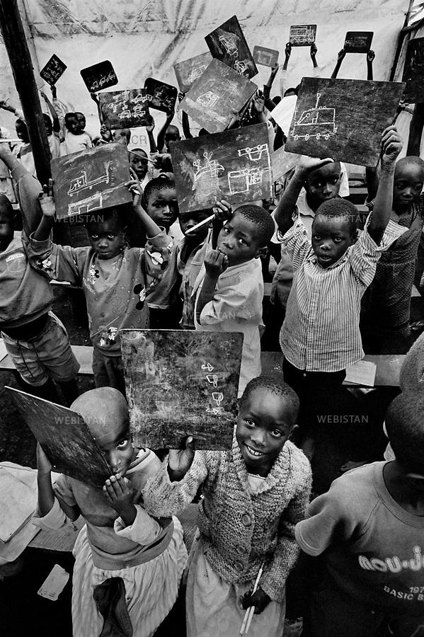 1995. Zaire. Democratic Republic of the Congo (DRC). Sud-Kivu Province. In a refugee camp, Rwandan Hutu children who fled their country during the 1994 Rwandan Genocide and who have lost their family, are at a school created by refugee teachers to maintain the education of the children. Zaïre. République Démocratique du Congo (RDC). Province du Sud-Kivu. Dans un camp de réfugiés, des enfants rwandais hutus qui ont fui leur pays pendant le génocide au Rwanda en 1994, et qui ont perdu leur famille, sont dans une école créée par des instituteurs réfugiés pour continuer l'éducation des enfants.