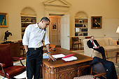 President Barack Obama talks to a Member of Congress on the phone in the Oval Office, Sunday, March 21, 2010. Assistant to the President for Legislative Affairs Phil Schiliro works in the background. .Mandatory Credit: Pete Souza - White House via CNP