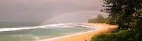 colorful rainbow against stormy tropical sky stretches over the sandy beach from the palm trees into the ocean