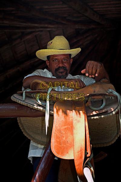Man leaning on a saddle, near Holguin, Cuba