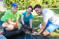 Salve Regina Service Plunge facilitators Brianna Connolly,'18, left, and Chris Chavarria,'19, right, work with Jeannette White,'20, while volunteering at the Methodist Community Gardens in Middletown.