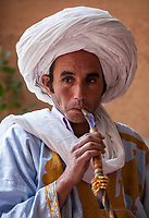 Near Ait Oudinar, Dades Gorge, Morocco.  Young Berber Man Smoking a Water Pipe.