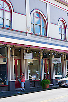 A woman strolls in front of Head Start, Kathmandu Trading Company and other businesses on Waianuenue Avenue, downtown Hilo, Big Island of Hawai'i.