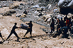 Two men pass luggage across a make-shift bridge after the main road between Dushanbe and Khorog in Tajikistan washed out. The road was out for a several days while the bulldozers worked to repair the road.