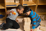 Education preschool 3-4 year olds two boys playing together in block area smiling and interacting