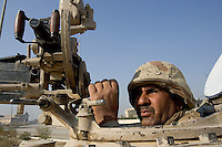 an Iraqi tank gunner from the 1st company, 1st armour battalion of the 1st mechanized Iraqi Army Brigade scans the neaby buinlings for possible insurgents while conducting  patrols, check points and observation posts on code name route Michigan, the main road of Ramadi in the week during the national election on TUE Dec 13 2005 in Ramadi, Iraq. 1st company is part of the first armor battalion of the New Iraqi Army. it has started its training in January 2005. after 50 days their 35 russian and chinese built T 55 tanks begun conducting operations under the guidance of a US military adivisor team. in April 2005 they patrolled in the Abu Ghraib area concluding their first significant mission. While these old tanks are rolling on the ramadi streets more modern T72s are getting ready to become fully operational in Taji, their main base. the Iraqi army wanted to show their power in ramadi during the Dec 15 elections displaying their new armour company. but like all the other Iraqi forces they are not going to secure the polling sites, staying in the rear with the rest of the iraqi and coalition forces. T 55s are very old tanks. production begun in the late 50s to the late 70s. athough obsolete many countries still use the T55 as their main heavy armoured combat vehicle. slow, heavvy and with very little room for the crew it suffers from many mechanical problems constantly challenging the iraqi mechanics and engineers.