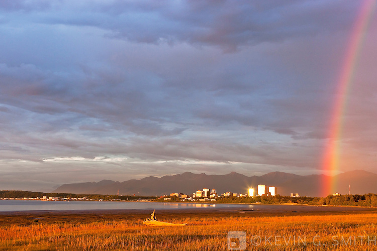 Rainbow over the Anchorage skyline, sunset light reflecting off the buildings, Knik Arm coastal mudflats in the foreground Chugach mountains in the background, Anchorage, Southcentral Alaska, Summer.