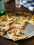 Pesto pizza with red and yellow peppers. Large round pie cut into squares on a pizza pan.