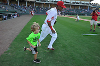 Right fielder Joseph Monge (15) of the Greenville Drive runs onto the field with a fan in a game against the Greensboro Grasshoppers on Wednesday, August 26, 2015, at Fluor Field at the West End in Greenville, South Carolina. Greenville won, 7-0. (Tom Priddy/Four Seam Images)