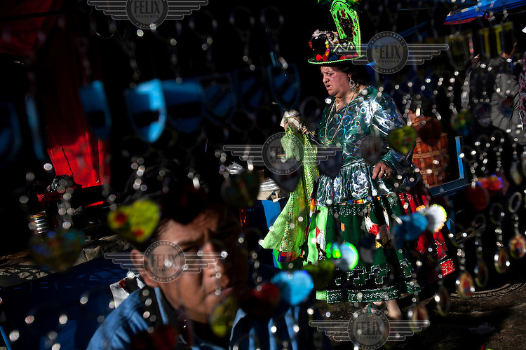 A woman wearing an elaborate costume dances at the Carnaval de Oruro. During the fiesta many people sacrifice llamas and give offerings such as coca leaves and cigarettes to show their dedication to the Devil, a Virgin, Pachamama or Mother Earth. The Devil (or Uncle) is a mythical character that protects the miners of Oruro who work in dangerous conditions hundreds of metres below the ground. During the carnival, people dress in outrageous costumes and dance for days before arriving at the Church of Socavon, where they pay their respects to a virgin. Ironically, many of the dancers wear devil costumes.