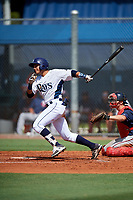 GCL Rays left fielder Raider Brito (25) follows through on a swing in front of catcher Austin Hale (70) during a game against the GCL Twins on August 9, 2018 at Charlotte Sports Park in Port Charlotte, Florida.  GCL Twins defeated GCL Rays 5-2.  (Mike Janes/Four Seam Images)