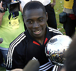 14 November 2004: Freddy Adu, holding the Alan I. Rothenberg Trophy, is engulfed by cameras after the game. DC United defeated the Kansas City Wizards 3-2 to win MLS Cup 2004, Major League Soccer's championship game at the Home Depot Center in Carson, CA..