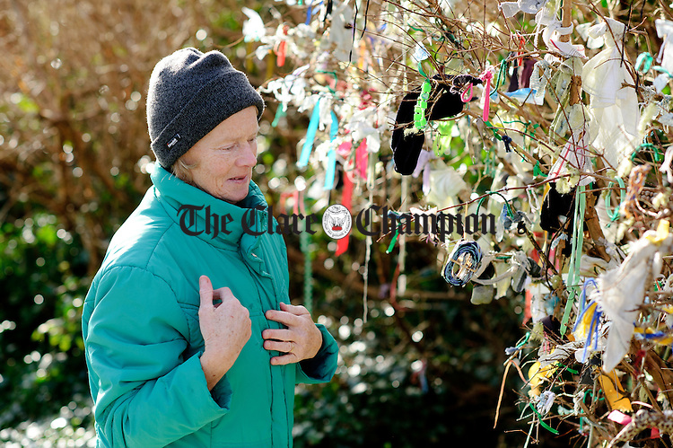 Kilmihil's Pauline Hehir blesses herself after hanging a memento on a bush during the annual celebration at St Bridget's Well. Photograph by John Kelly.