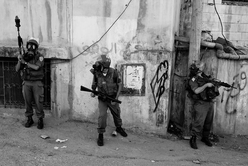 Israeli soldiers stand in a laneway during violent clashes with Palestinian protestors near the Qalandiya checkpoint by the city of Ramallah, The West Bank, Friday October 9, 2009. Israel had denied Palestinians entry to Jerusalem's Old City after a week of high tension regarding access to the city's holy sites. Photo: REUTERS/Ed Giles (West Bank).