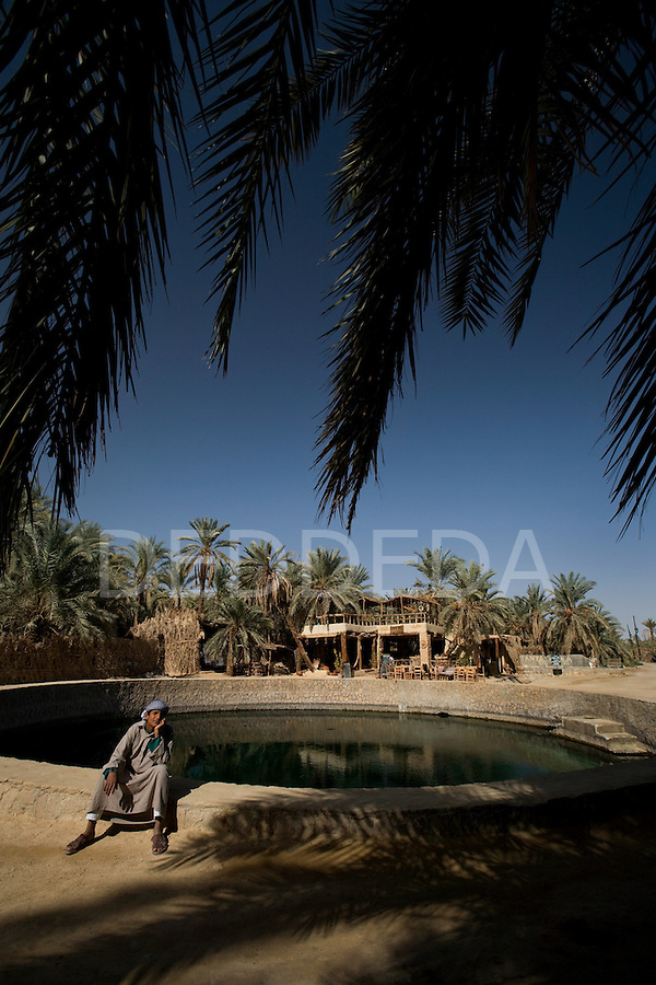 A local Siwan young man dressed in traditional clothing sits next to Cleopatra's Bath , a natural and warm spring in Siwa Town of the Siwa Oasis, Egypt.