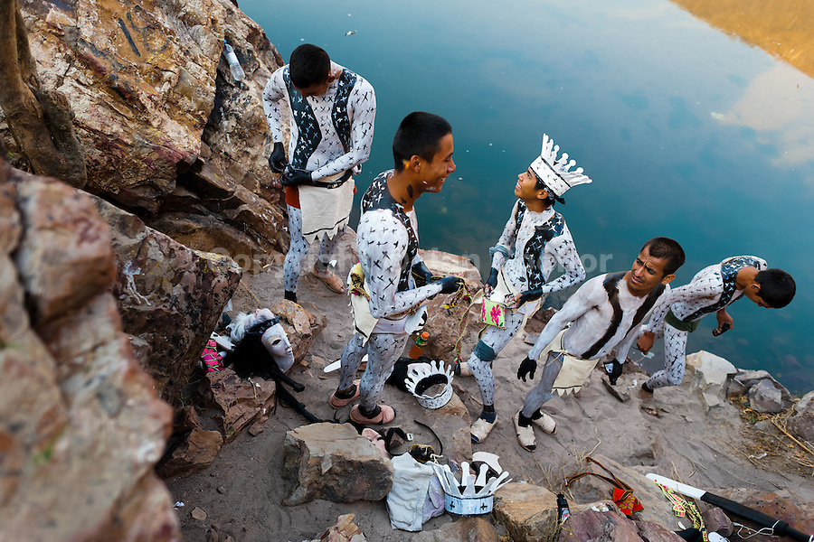 "Cora Indian boys, painting each other their bodies, prepare themselves for the sacred ritual ceremony of Semana Santa (Holy Week) in Jesús María, Nayarit, Mexico, 21 April 2011. The annual week-long Easter festivity (called ""La Judea""), performed in the rugged mountain country of Sierra del Nayar, merges indigenous tradition (agricultural cycle and the regeneration of life worshipping) and animistic beliefs with the Christian dogma. Each year in the spring, the Cora villages are taken over by hundreds of wildly running men. Painted all over their semi-naked bodies, fighting ritual battles with wooden swords and dancing crazily, they perform demons (the evil) that metaphorically chase Jesus Christ, kill him, but finally fail due to his resurrection. La Judea, the Holy Week sacred spectacle, represents the most truthful expression of the Coras' culture, religiosity and identity."
