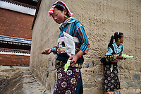 Young Tibetan Buddhist pilgrim girls walk among the housing complexes outside of the Labrang Monastery in Xiahe, Gansu, China.  Xiahe, home of the Labrang Monastery, is an important site for Tibetan Buddhists.  The population of the town is divided between ethnic Tibetans, Muslims, and Han Chinese.