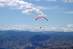 A paraglider flies over dry eastern Washington hills near Lake Chelan. The Cascade Mountain Range is in the background.