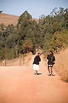 Two young girls walking to school down a dusty road in Pine Valley, Swaziland. The Kingdom of Swaziland (population 1.1m), a small, landlocked country in southern Africa was bordered by South Africa on three sides and Mozambique to the east, with Mbabane as its administrative capital. At the start of the 21st century, the country had the highest incidence per head of population of HIV/Aids in the world and and high levels of poverty mainly in rural areas where 75 per cent of the population lived.