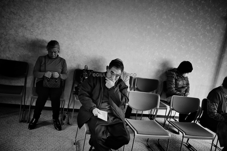 Local residents of Taro new community waiting in the old temporary clinic provided by MSF, December 2011..In the north east of Japan there is a small city called Taro that was completely destroyed by the tsunami on the 3/11. After the tsunami the whole population of 8000 people moved to the top of the mountain where they settled down.  .Here they had temporary housing, temporary shops, a japanese warm bath and a temporary clinic provided by MSF. Almost one year later they are still living there, they have created their own new little community village and this has became the new reality for them. In this small colony you can find barber shops, restaurants, grocery stores, schools and a playground just like a normal village. The colony is not far from the sea so, as the majority of the population from Taro are fishermen, they don't find it too hard to survive in their new environment. From a temporary shelter this has became the new TARO Village.
