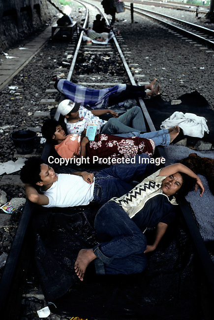 Homeless youths sleep on the railroad tracks February 25, 1998 in central Jakarta, Indonesia. Indonesia was hit by economic turmoil during the emerging market crisis of 1998, and the currency, the rupiah, lost a lot of its value. Many people lost their jobs and many from the countryside came to the big cities to look for work. (Photo by: Per-Anders Pettersson)