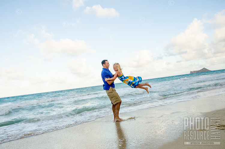 A father playfully swinging his daughter around on Waimanalo Beach, O'ahu.