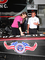 Apr 24, 2015; Baytown, TX, USA; NHRA top fuel driver Steve Torrence (right) with Taya Kyle , wife of slain US Navy sniper Chris Kyle in the pits during qualifying for the Spring Nationals at Royal Purple Raceway. Torrence announced a partnership with the Chris Kyle Frog Foundation. Mandatory Credit: Mark J. Rebilas-