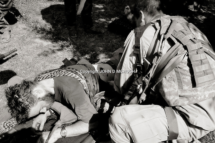 "Photojournalist John D McHugh grimices in pain as a medic examines and dresses his gunshot wound at Kamu Outpost in Nuristan, in north-east Afghanistan, 14 May 2007. The photographer was shot through the stomach during a firefight between the US and Afghan National Army (ANA), who he was embedded with, and insurgents. 17 ANA died, one is still recoreded as ""missing in action"", and 4 more were wounded. 7 US soldiers were also wounded in the fight. (John D McHugh)"