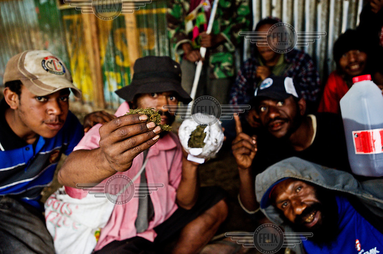 A man, sitting among a group, shows a sample of marijuana taken from a bag. Marijuana, which grows in copious quantities around Goroka, is smuggled out aboard ships operated by logging companies. The marijuana is then traded for for arms from post conflict countries in Asia.