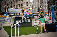 """Visitors sit on an over-sized park bench in Flatiron Plaza in New York on Saturday, June 20, 2015. The bench is a promotion ofr the AOL program """"Park Bench"""" with Steve Buscemi. The show is basically an internet talk show where Buscemi talks with varied guests on a park bench, not in a studio. (© Richard B. Levine)"""