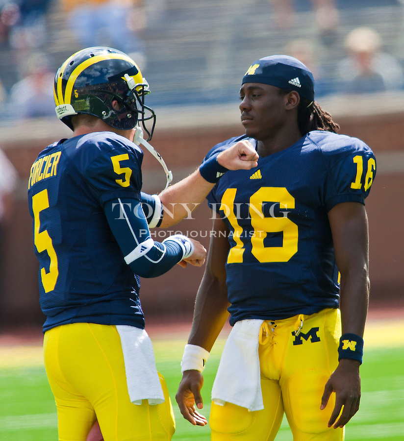 Michigan quarterbacks Tate Forcier (5) and Denard Robinson (16) talk before an NCAA college football game with with Connecticut, Saturday, Sept. 4, 2010, in Ann Arbor, Mich. (AP Photo/Tony Ding)